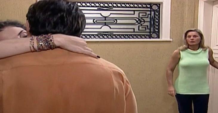 Helena ficará furiosa ao ver o filho em momento quente com a vizinha na porta do apartamento