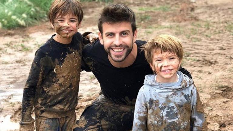 O jogador do Barcelona Gerard Piqué se diverte na lama com os filhos